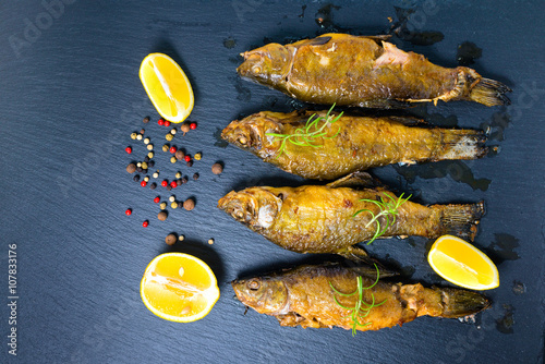 Valokuva  top view of fried tench fish served with aromatic rosemary, lemon and dry pepper
