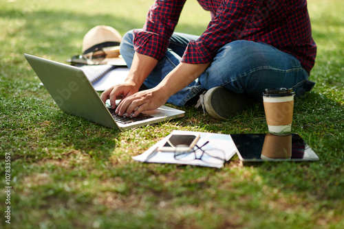 Fotografia  Cropped image of student sitting on the ground and working on laptop