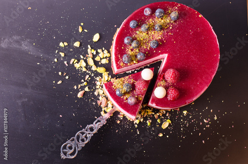 Delicious raspberry cake with fresh strawberries, raspberries, blueberry, currants and pistachios on black background.