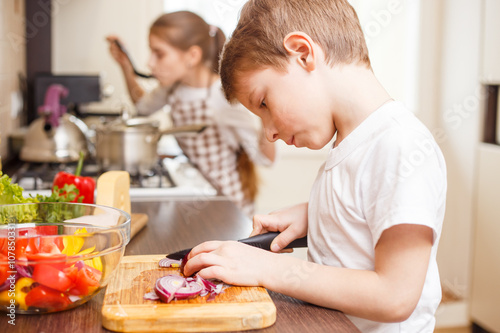 Foto op Plexiglas Koken Small boy cooking together with his sister