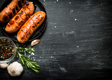 Fried Sausages With Garlic And Herbs In A Pan.