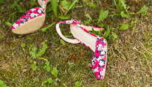 Shoes Of A Woman On Green Grass. Summer Holiday Concept, Daylight