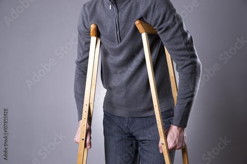 Fotografia Man on crutches on a gray background