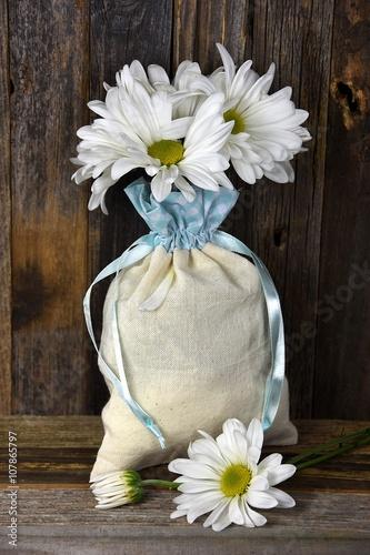 Fotografie, Obraz  daisy bouquet in muslin bag on rustic wood