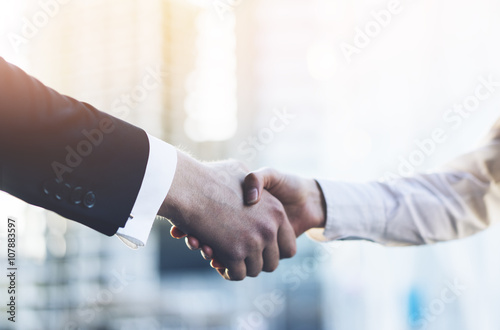 Cuadros en Lienzo  Closeup image of business partners making handshake outdoors, modern office or s