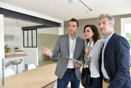 Fotografie, Obraz  Mature couple with real-estate agent visiting new house
