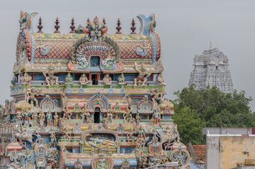 Trichy, India - October 15, 2013: The Vellai Gopuram at the Sri Ranganathar Swamy sanctuary, stands in the background of a more common Gopuram full of statues including the main Ranganathar.