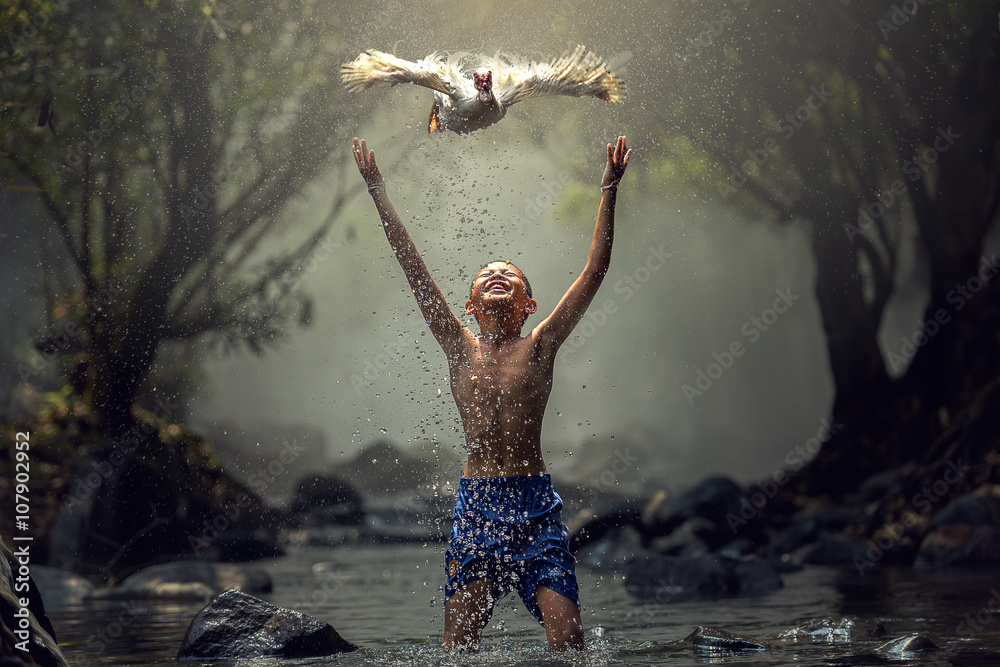 Fototapeta Children playing catch duck in river
