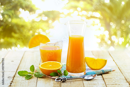 plakat Glass and pitcher of orange juice on wooden, on green nature background