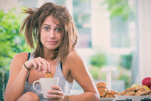 obraz lub plakat Young messy woman have breakfast in the kitchen