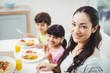 Portrait of smiling mother with children at dining table