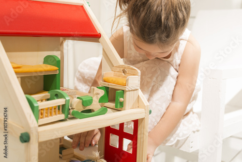 Photo  Cute little girl playing with dollhouse