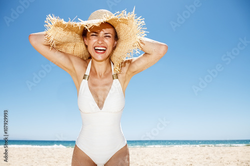 Obraz na płótnie Smiling woman in white swimsuit and straw hat at sandy beach