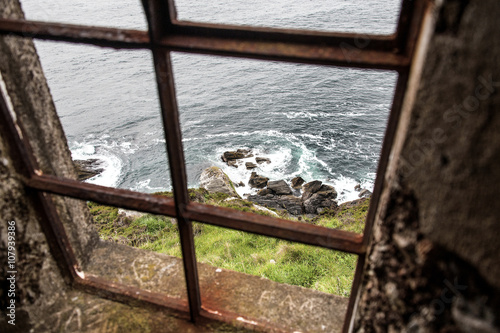Plagát  View out of an old lighthouse window down to the ocean coast