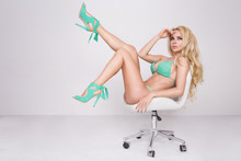Slim Beautiful Woman Long Blond Hair Sitting On A Chair With Long Legs Raised Up In Heels Blue Green