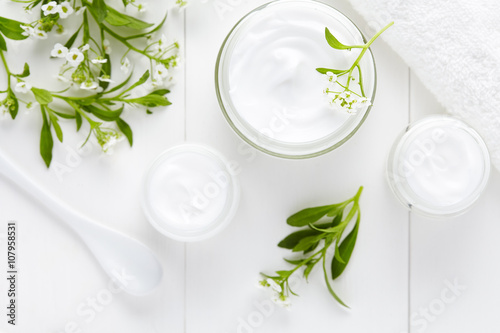 Obraz Medical therapy cosmetic cream with herbal flowers hygienic skincare product wellness and relaxation mask in glass jar on white background - fototapety do salonu