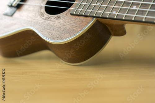 Close up of wooden ukulele on wooden background #107958710