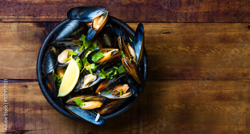 Photo  Mussels in clay bowl on wooden dark background