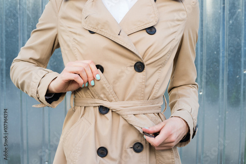 Fotografie, Tablou  Female hand tie belt on a coat outdoors