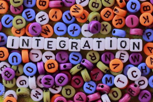 Fotografía  Makroaufnahme von bunten Runden BUCHSTABEN en deren Mitte auf das Wort Weissen Würfeln Integración liegt