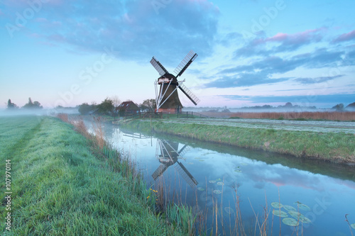 Poster Mills Dutch windmill by river at sunrise