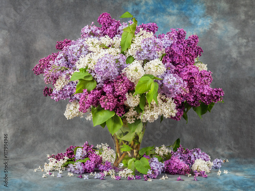 Photo sur Toile Lilac Lilac in a vase on the table. Dramatic light.