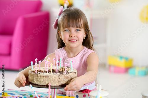 Zdjęcie XXL Szczęśliwa mała dziewczynka z smakowitym tortem przy przyjęciem urodzinowym