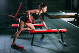 woman exercising dumbbell row at the gym