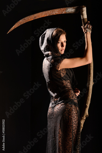 Photo  Girl in a black lace smock with scythe of death.