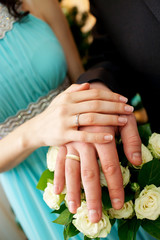 Obraz na płótnie Canvas Hands of the groom and bride with rings and bridal bouquet