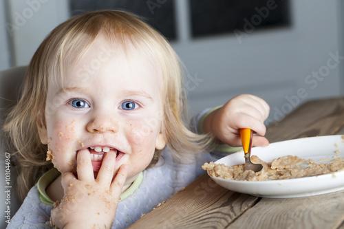 Foto op Canvas Kruidenierswinkel Baby eats porridge spoon mashed