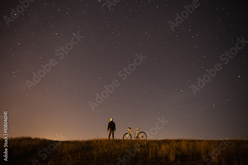 Poster Marron chocolat starry sky, night photography, astrophotography, the silhouette of a man, a man standing next to a mountain bike on the background of a starry sky, the white bicycle