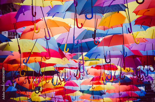 Colorful umbrellas hanging above the street Плакат
