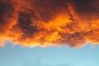 Leinwandbild Motiv Orange and Gold Cloud at Sunset Against a Blue Sky