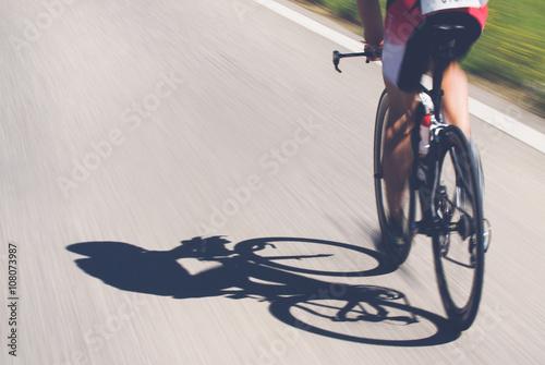 Fotobehang Fietsen Speedy shadow - A cyclist at top speed on the triathlon race.