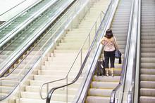 Hispanic Woman Standing On Escalator