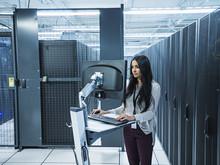 Mixed Race Technician Using Computer In Server Room