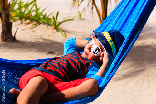 happy little boy relaxed in hammock on beach