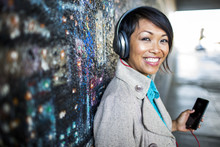 Woman Listening To Cell Phone By Mural
