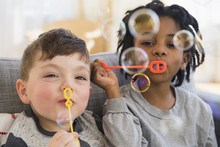 Close Up Of Boys Blowing Bubbles On Sofa