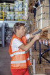 young smiling warehouse worker running inventory check