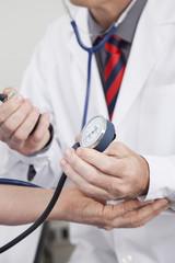 Doctor taking blood pressure of senior woman