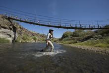 Caucasian Woman Fishing In Rural River