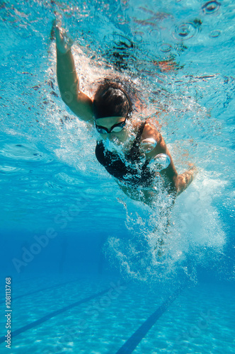 Young female athlete swimming freestyle in the pool Wallpaper Mural
