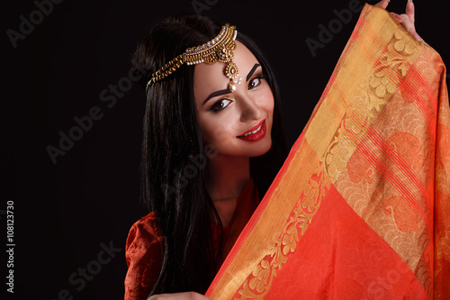 234c237dad Beautiful Young Indian Woman in red Traditional Clothing with perfect Makeup  and Oriental Jewelry.