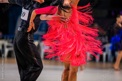 Foto op Aluminium Dance School athletes couple of dancers on ballroom dance contest. bright red dress girl