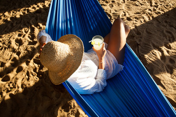 Young woman lying in straw hat on beach