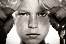 Child With Boxing Gloves Focusing On Punching Pad