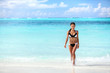 Beach sexy bikini Asian woman coming out of water walking relaxing on tropical getaway paradise. Young ethnic model with slim weight loss body sunbathing in summer vacation travel.