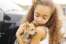 Mixed Race Girl Petting Dog Ou...